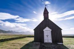 Sun sube detrás de la iglesia de Budakirkja en una mañana hermosa en la península de Snaefellsnes, Islandia Foto de archivo libre de regalías