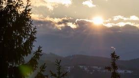 Sun sube sobre las nubes y paisaje del bosque en lapso de invierno Mañana dramática con los árboles que se mueven en viento almacen de metraje de vídeo