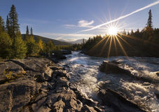 Sun with sun rays giving golden glow to river landscape. Staying in the kvikkjokk fjallstation giving me full opportunity to photograph this beautiful tarraatno stock image