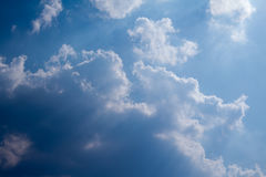 Sun with sunbeams in a beautiful cloudy sky. blue sky is covered by white clouds Royalty Free Stock Photos