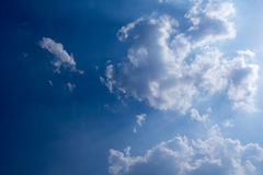 Sun with sunbeams in a beautiful cloudy sky. blue sky is covered by white clouds Stock Photo