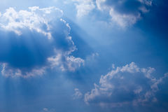 Sun with sunbeams in a beautiful cloudy sky. blue sky is covered by white clouds Royalty Free Stock Images