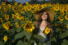 Sun, sunflowers, and a pretty smile. Many emotions being experienced by the girl;  joy, happiness, contentment, glad to be alive Stock Images