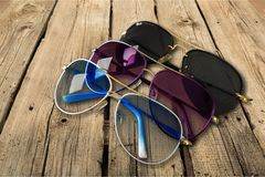 Three sunglasses on wooden background, close-up royalty free stock photography