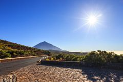 Sun with sunlight over mountains on blue sky with fog and Teide volcano, Tenerife Royalty Free Stock Photography