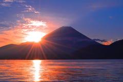 The Sun of sunrise and Mount Fuji from Lake Motusu JAPAN stock photo