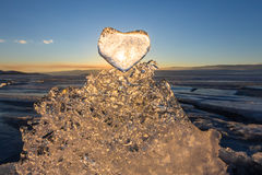Sun at sunset shines through the icy heart on texture transparen Stock Image