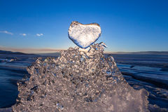 Sun at sunset shines through the icy heart on texture transparen Royalty Free Stock Image