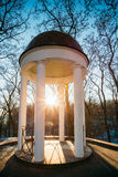 Sun at sunset shining through gazebo in city park Stock Image