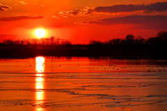 Sun in Sunset Sky over Frozen Winter Lake Stock Images