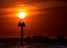 Sun sur le marqueur de bateau, ciel rouge de coucher du soleil Photographie stock libre de droits