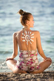 Sun symbol. Written in sunlotion on womans back on beach Royalty Free Stock Photo