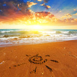 Sun symbol on a sandy beach Stock Images