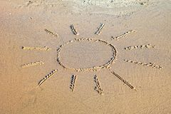 A sun symbol written in the sand. Stock Photos