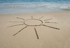 Sun symbol written in the sand on tropical beach Royalty Free Stock Photo