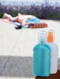 Sun tan lotion cream. Closeup of a sun tan lotion or cream with a woman sunbathing in the background stock photography