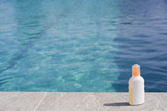 Sun tan lotion poolside Stock Photo