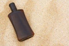 Sun tan oil on sand Stock Photography