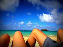 Sun Tanned Legs on a Romantic Beach Tropical Vacation Honeymoon. Looking out over the turquoise waters and white sand beach on a beautiful sunny day. Couple Royalty Free Stock Photos