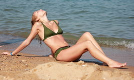 Sun Tanning. Women in green swimsuit, sun tanning on the beach Royalty Free Stock Photography
