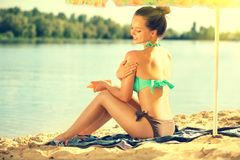 Sun tanning. Beauty young woman applying suntan lotion. Beautiful happy cute girl applying sunscreen solar cream on her skin stock image