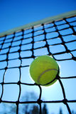 Sun Tennis. A tennis ball stuck in a net with the sun backlighting Stock Photography