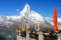 Sun terrace underneath mountain. ZERMATT - JUNE 26: Beautiful weather invites visitors on the sun terrace with impressive views on the famous mountain Matterhorn Royalty Free Stock Images