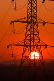Sun thru pylon. Setting Sun seen through an electricity pylon royalty free stock image