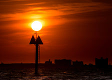Sun on top of boat marker, red sunset sky royalty free stock photography