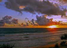 The sun touches the horizon on the tropical coast. stock photography