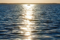 Sun track and fishing boat on lake surface. Royalty Free Stock Image