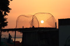 The sun in the trap. The sun during sunrise shines through in a fishing trap, lying on the roof of the building in the fishing cooperative in Old Town Area. Umm stock photography