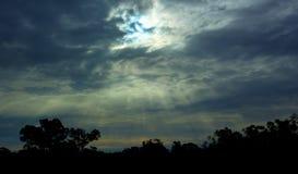 Sun traversant des nuages avec la silhouette des arbres photographie stock