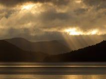 Sun a través de las nubes sobre el lago Fotografía de archivo libre de regalías