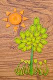 Sun, tree and flowers made of leek and carrot slices on wooden cutting board background. Stock Photography