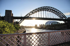 Sun on the Tyne. The metal latticework of the handrail of the Swing Bridge is in the foreground. The silhouette of the Tyne Bridge forms the main of the image Stock Image