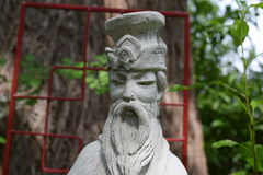 Sun Tzu statue in front of red garden arbor. And tree in the background Stock Image