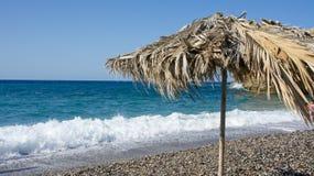 Sun umbrella. On the sand beach near blue sea Royalty Free Stock Photo