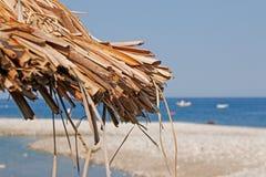 Sun umbrella and beach beds on coastline Stock Photography