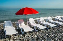 Sun umbrella and beach beds on the shingle beach Royalty Free Stock Image