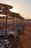 Sun umbrella and beach beds on tropical coastline Royalty Free Stock Photos