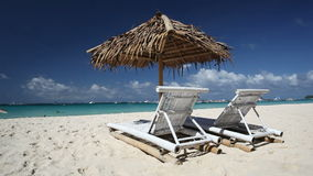 Sun umbrella and beach chairs on coastline with white sand. Boracay stock footage