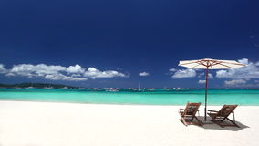 Sun umbrella and beach chairs on coastline with white sand. Boracay stock video footage