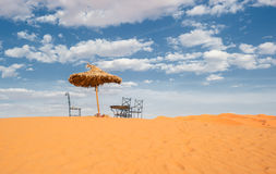 Sun umbrella and chairs in desert Royalty Free Stock Image