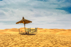 Sun umbrella and chairs in desert Stock Photography