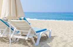 Sun umbrella and chaise longue on sea beach. White sand and sea in tropical resort Stock Image
