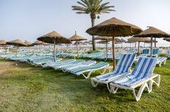 Sun umbrella on an empty beach and sea water horizon. Clear blue sky. Stock Image