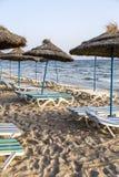 Sun umbrella on an empty beach and sea water horizon. Clear blue sky. Royalty Free Stock Image