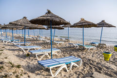 Sun umbrella on an empty beach and sea water horizon. Clear blue sky. In tunisia Stock Photo
