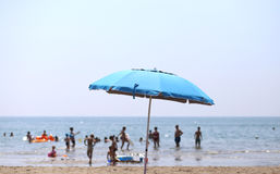 Sun umbrella and many people playing in the sea water in summer Stock Photo